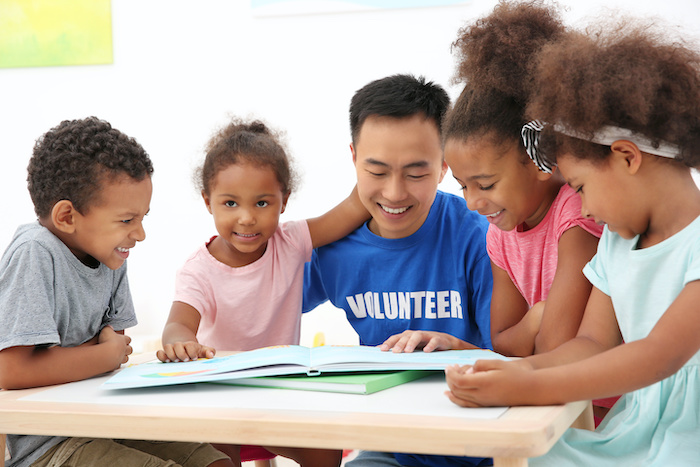 volunteer surrounded by children reading books at table