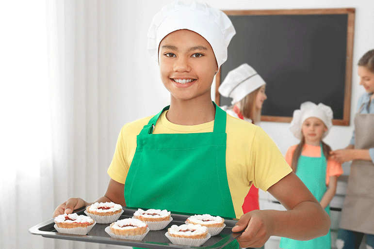 tween chef with chefs hat and apron holding a tray of dessert