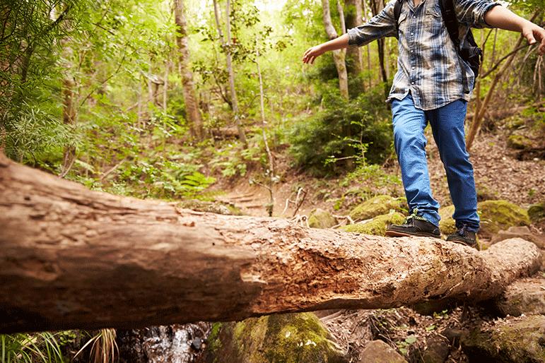 young boy walking across log in woods