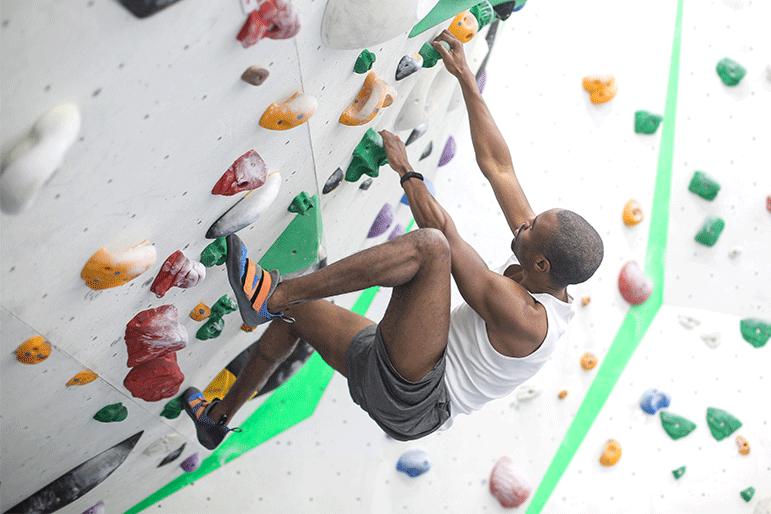 man climbing a rock wall and gripping tightly with hands