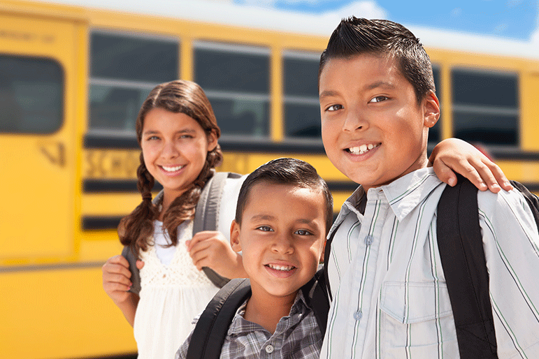 two elementary school brothers and a sister smile to camera outside of their school bus